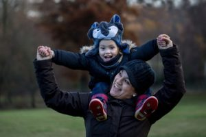 A boy plays on his mum's shoulders during a family photographer London session