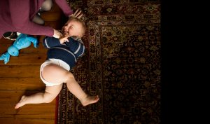 A baby is tickled by his mummy during a family photographer North London photoshoot