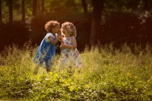 Two friends whisper secrets in a park during a family photographer London session