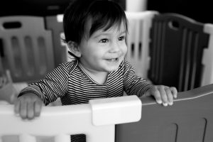 A boy smiles in his playpen during a family photographer London session