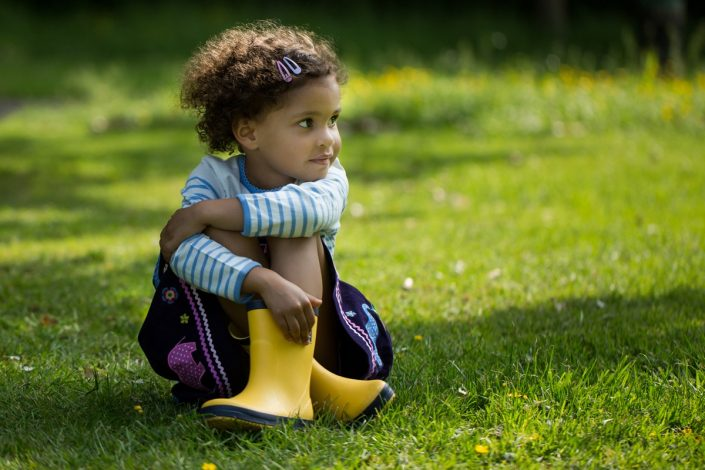 A girl sits down on the grass during a sunny day in Waterlow Park highgate