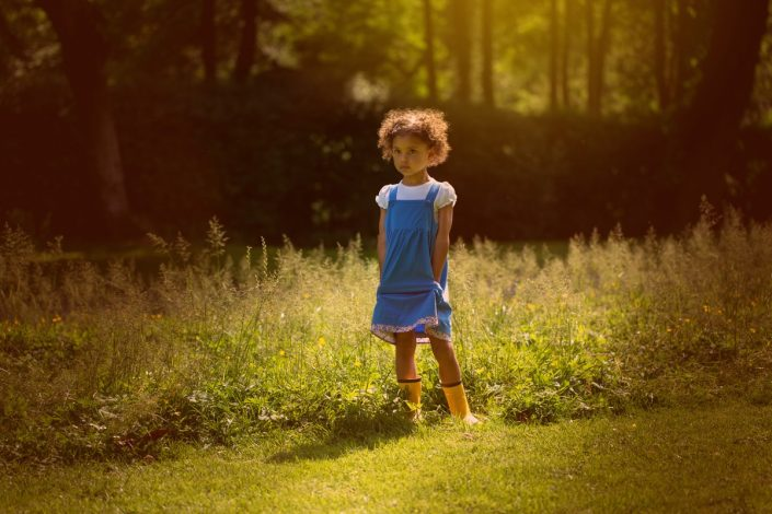 A girl stands soulfully thinking during a park photoshoot North London