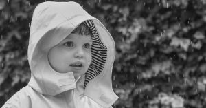 A boy wears a rain jacket as it rains in his back garden for a North London family photoshoot