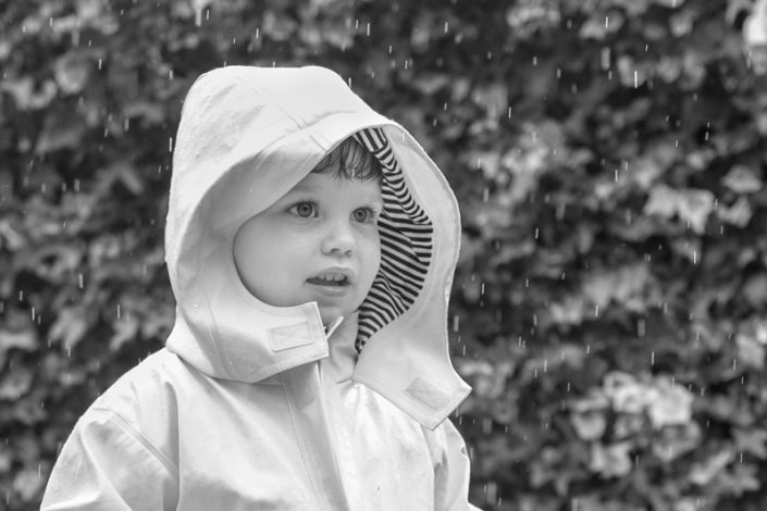 outdoor family photography: A boy makes the most of the rain in his back garden