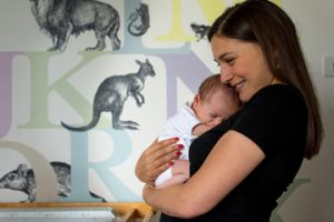 A mum cuddles her newborn just weeks after birth during Muswell Hill baby photographer session