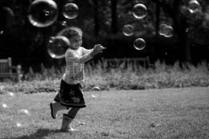 Outdoor family photoshoot: A black and white image of a girl popping bubbles
