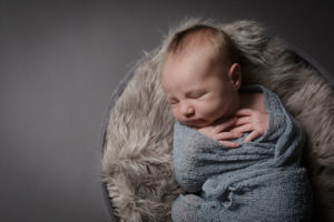 Baby photographer Muswell Hill photoshoot, in studio, with baby wrapped in grey.
