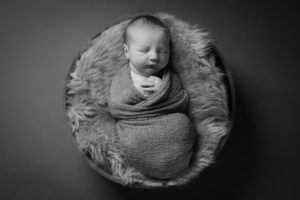 A black and white photo of newborn baby asleep during a north London photographer session