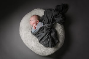 When babies are awake, they can be wrapped in beautiful linens during their baby photographer Muswell Hill session