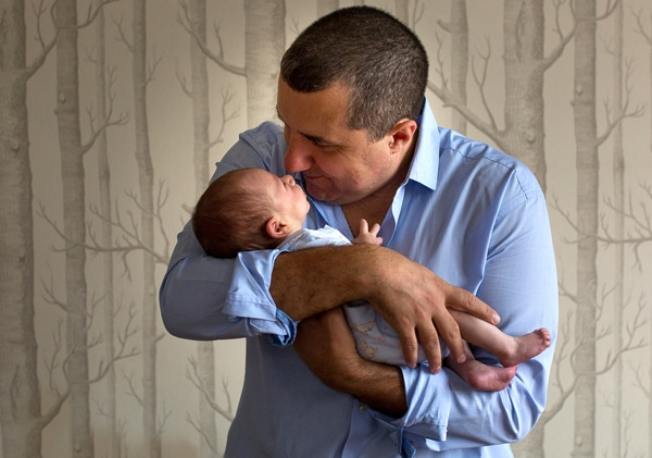 Dad cuddles baby as part of newborn photography session in Muswell Hill