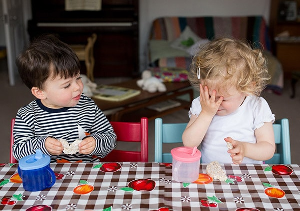 Twins chat to each other over snack time during their family photoshoot North London