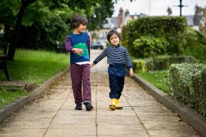 Two boys walk down the path deep in conversation during a children photographer London session
