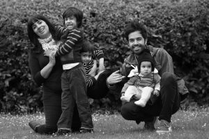 A family of five pose for a family photoshoot in the park