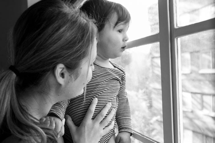 A boy stares out the window with his mum holding him during a family photographer London session