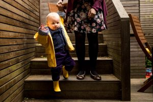 A baby boy waves at the camera as he walks carefully down the steps during a family photographer North London session
