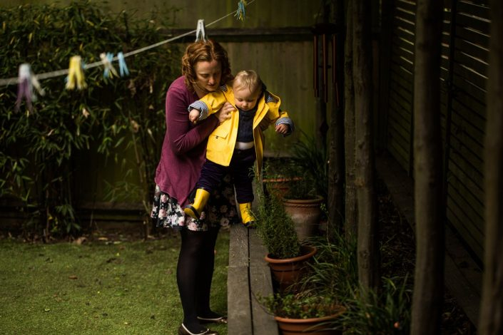 A baby attempts to walk along the wall with mother's help during a back garden photoshoot