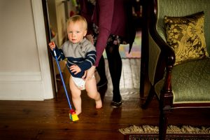 A boy pretends to sweep the floor during a family photoshoot North London