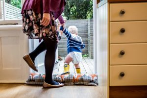 A baby boy cannot wait to go outside even in just his nappy, during a family photoshoot north London