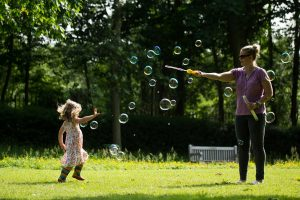 Family photographer north London: A mum blows bubbles for her daughter in the park
