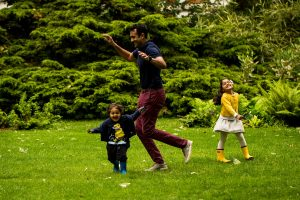 A dad runs around with his daughter and younger son during a family photographer North London session