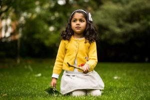 A girl plays with a stick in the park during a children photographer London session
