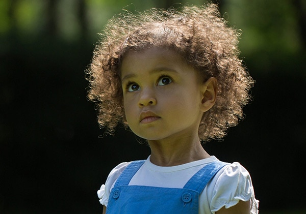 A girl looks up to the sky on a sunny day in Waterlow Park, Highgate, during a family photographer London session