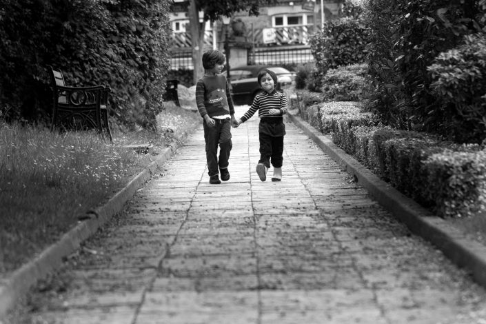 Brothers hold hands as they walk up the park path during a family photoshoot North London