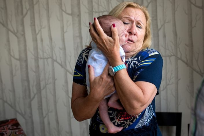 A loving grandmother cradles her grandson during a family lifestyle photography session