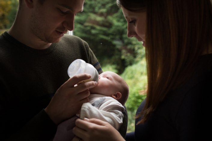 Family photoshoot north London: Dad feeds baby the bottle during session