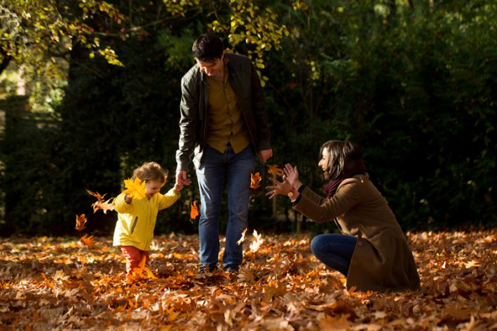 A family play with the autumnal leaves during a park photoshoot