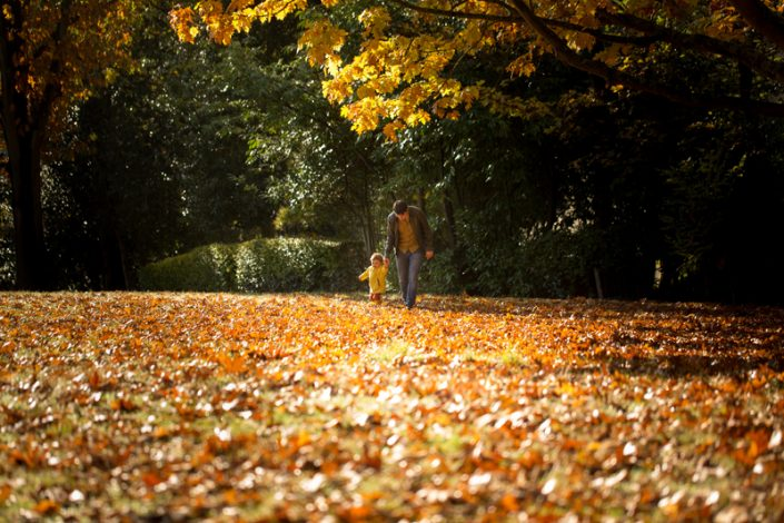 A girl and her daddy walk through the autumn leaves in Waterlow Park, Highgate