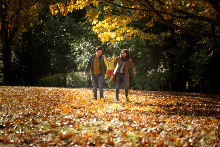A girl is lifted up among the autumn leaves by her parents during a family photographer North London shoot