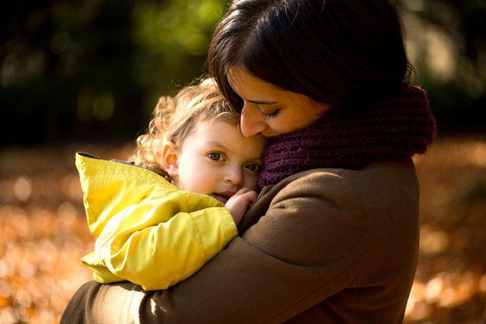 A mum holds her little girl close during a playful family photoshoot North London