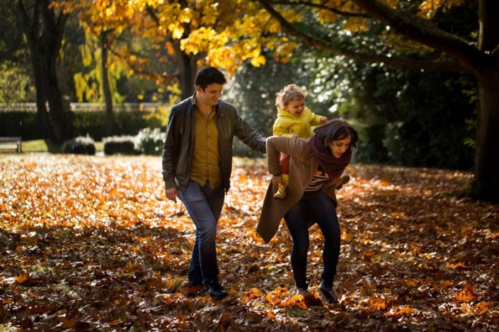 Mum gives daughter a piggyback among the autumn leaves