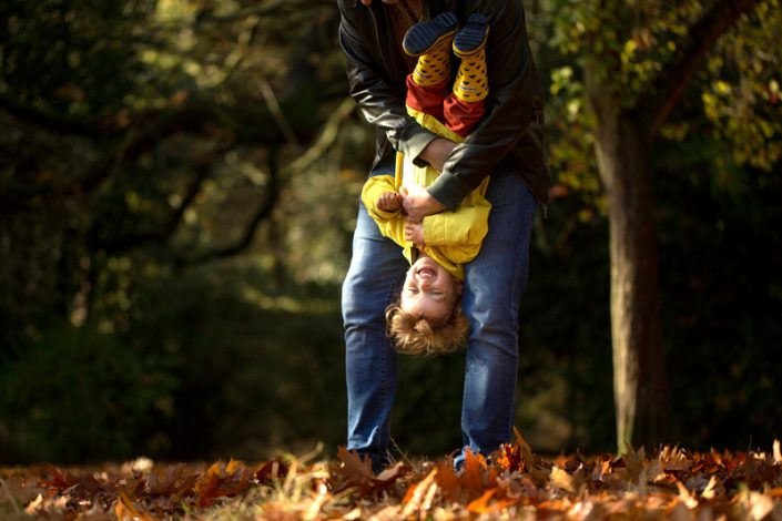 A girl is held upside down during her outdoor family photoshoot