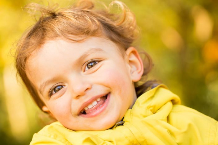 A girl laughs at the camera during an outdoor family photography session
