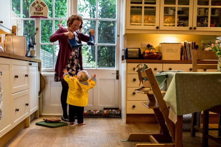Mum finds her baby boy's wellies to go out in the garden during a family photoshoot North London