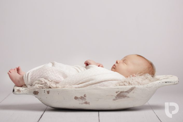 A baby fits in a small basket as part of a photoshoot in a North London photographer studio