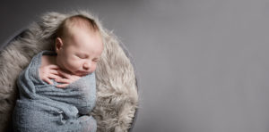 A newborn baby sleeps on a soft blanket with a grey backdrop during a Muswell Hill baby photography session