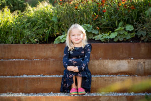 Girl sits on steps for a family photographer North London