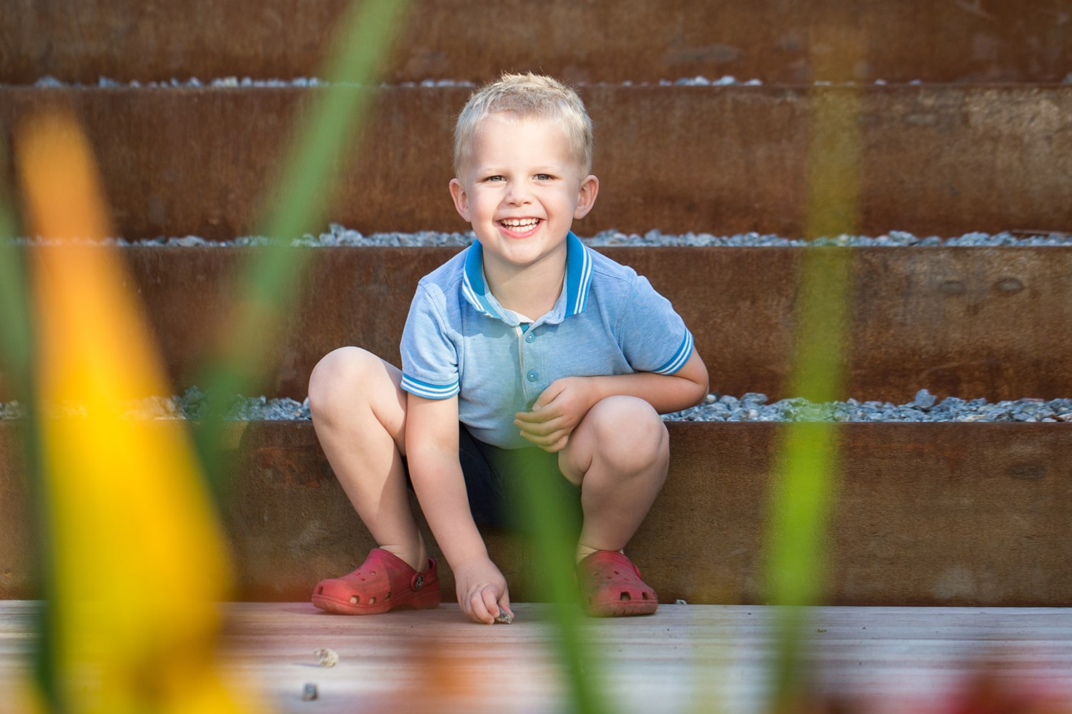 A boy plays with some stone during an outdoor family photography session