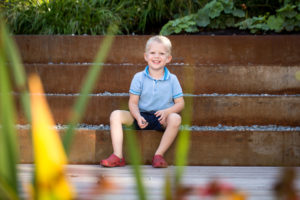 Boy laughs on steps during a children photographer London session