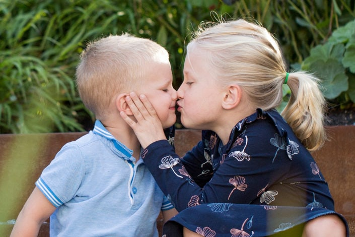Outdoor family photography session: Siblings kiss each other in a lovely moment during the photoshoot