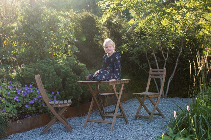 Girl poses in the sun on a table for the best family photographer North London