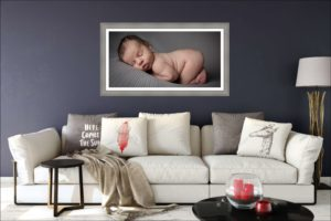 A gorgeous print of a sleeping newborn baby hangs above a comfy living room sofa in Muswell Hill