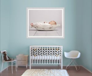 A statement wall art from Louisa Peacock Photography hangs in baby's nursery