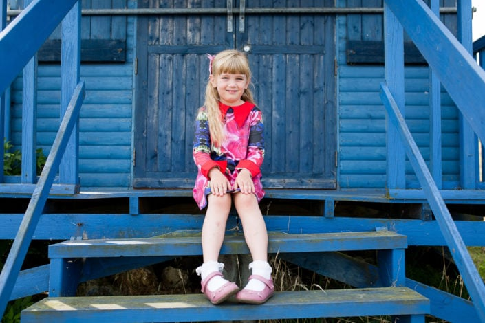 A girl sits quietly during a family photography session