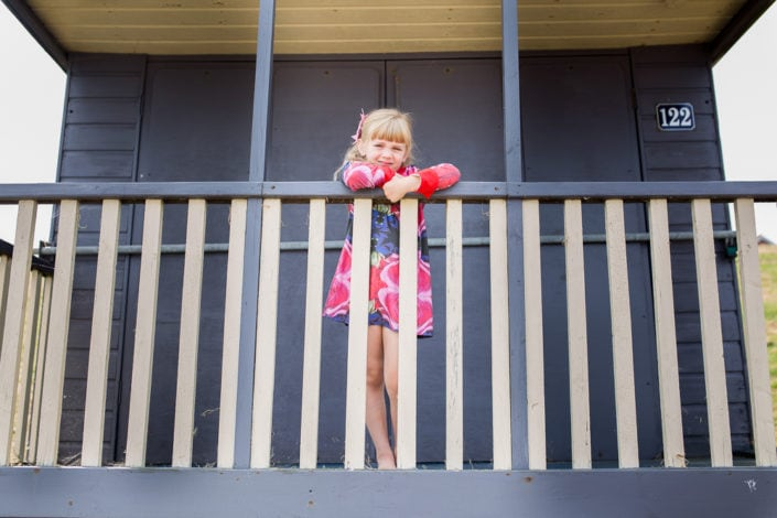 A girl hangs over the bar of a purple beach hut during an outdoor family photoshoot