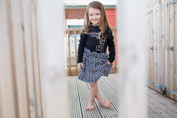 A girl wears her favourite dress during an outdoor family photoshoot