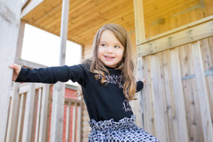 A little girl hangs out on a beach hut during an outdoor family photoshoot